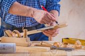 Carpenter scetching wooden plank — Stock Photo