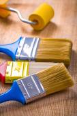 Three paint brushes and roller — Stock Photo