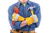 Tools in crossed arms of worker — Stockfoto