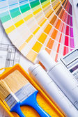 Rolled blueprints and paint brushes — Stock Photo