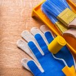Gloves paint roller tray and brushes — Stock Photo #72716145
