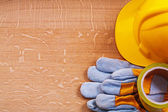 Safety tape protective gloves and hard hat — Stock Photo