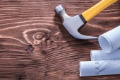 Claw hammer and blueprints on board — Stock Photo