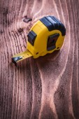 Yellow tape-measure on  wooden board — Stock Photo