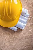 Building helmet and blueprint rolls — Stock Photo