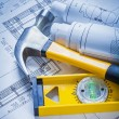 Construction level, claw hammer, blueprints — Stock Photo #73634075