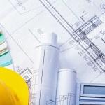 Yellow helmet rolled blueprints calculator — Stock Photo #73635145