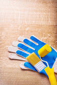 Blue working gloves with paint brush — Stock Photo