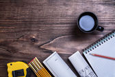 Copybook, pencil, blueprints and cup of coffee — Stock Photo