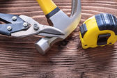 Hammer, cutting pliers and tape line — Stock Photo
