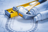 Construction level, claw hammer and blueprints — Stock Photo