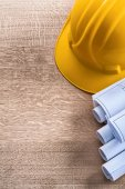 Construction helmet and blueprint rolls — Stock Photo