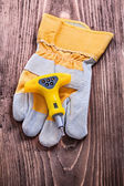 Insulated electric screwdriver and protective glove — Stock Photo