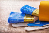 Two paint brushes and working gloves — Stock Photo
