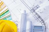 Yellow helmet rolled blueprints calculator — Stock Photo