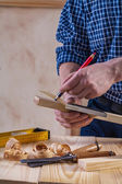 Carpenter scetching plank — Stock Photo