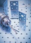 Drilled angle fasteners and metal drill — Stockfoto