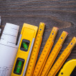 Blueprint rolls, construction level and wooden meter — Stock Photo #78562064