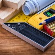 Square ruler, blueprints and wooden meter — Stock Photo #78563148