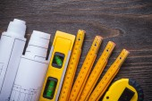 Blueprint rolls, construction level and wooden meter — Stock Photo