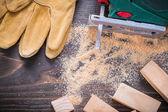 Electric jigsaw sawdust, working gloves — Stock Photo