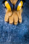 Leather safety gloves and ear muffs — Stock Photo