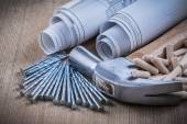 Blueprint rolls, hammer, dowels and nails — Stock Photo