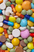 Pile of colorful medications tablets - medical background — Stock Photo