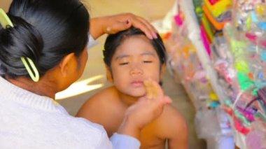 BAGAN, MYANMAR - CIRCA JAN 2014: Mother applies sunscreen thanaka on her daughter's skin — Stock Video