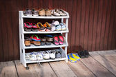 Colorful Shoes on a Plastic Shoe Rack, Outside a House — Stock Photo