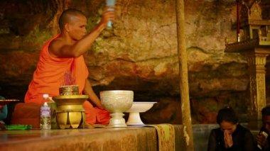 PHNOM KULEN. CAMBODIA - CIRCA DEC 2013: Buddhist monk in traditional orange robe doing religious ritual for worshippers in Cambodia. Asia. — Stock Video