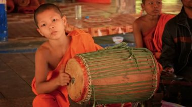 SIEM REAP. CAMBODIA - CIRCA DEC 2013: Young Cambodian monk playing a traditional music on typical. handmade. Khmer drum in Angkor Wat temple. — Stock Video
