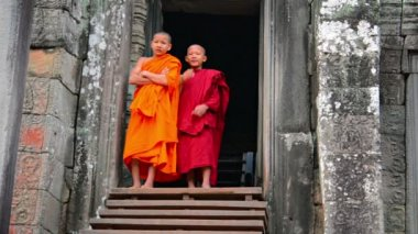 SIEM REAP. CAMBODIA - CIRCA DEC 2013: Two child monks in traditional robes are conscious of the camera as they stand in the doorway to Bayon Temple in Siem Reap. Cambodia. — Stock Video