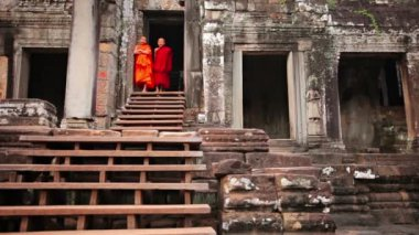 PHNOM PENH. CAMBODIA - CIRCA DEC 2013: Two Cambodian children in monks robes standing at the top of the wooden steps leading to the entrance of Bayon Temple in Siem Reap. Cambodia. — Stock Video