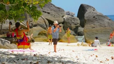 SIMILAN ISLANDS. THAILAND - CIRCA FEB 2015: Tourists participating in various activities on a beach. including a rope swing. amateur photography and playing in the sand in the Similans of Thailand — Stock Video