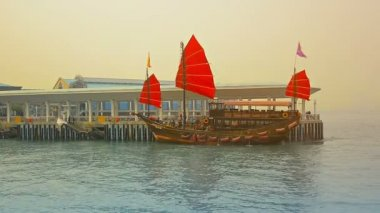 HONG KONG. CHINA - CIRCA JAN 2015:  Tour boat. patterned after an old fashioned Chinese sailing junk. arriving to take on passengers in Victoria Harbor. Hong Kong. — Stock Video