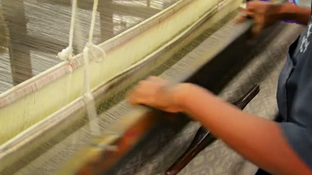 Local artisan weaving beautiful patterns by hand on an old-fashioned. wooden loom. — Vídeo de stock