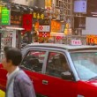 Long line of red and white taxis waits for passengers at a busy shopping area in downtown Hong Kong. — Stock Video #77356660