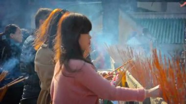 Buddhist worshippers leaving smoldering incense sticks at an alter at Wong Tai Sin Temple in Hong Kong — Stock Video