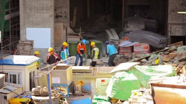 Laborers in hardhats. working at a construction site in downtown Hong Kong. — Stock Video