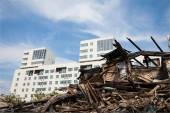 Old ruined wooden house on the background of the new buildings — Stock Photo