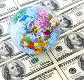 Globe and dollars — Stock Photo
