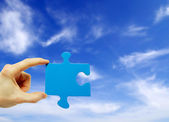 Puzzle in hand on sky background — Stock Photo