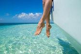 Women's legs and  sea — Stock Photo