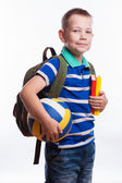 Happy schoolboy with backpack, ball and books isolated on white background — Stockfoto