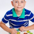Cute little boy playing puzzles at the table — Stock Photo #55957181