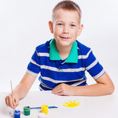 Happy cheerful child drawing with brush in album using a lot of — Stock Photo