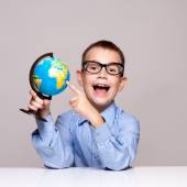 Portrait of a little boy holding a globe. Travel concept — Stock Photo