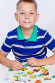 Cute little boy playing puzzles at the table — Stockfoto