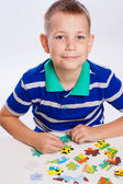 Cute little boy playing puzzles at the table — Stock fotografie